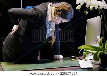 Close-up view of a woman-reception worker hotel manager with pain in kidneys on gray background. Young woman with back ache clasping her hand to her lower back. Woman suffering from ribbing pain, waist pain. stock photo