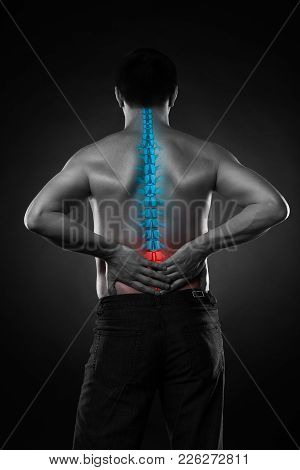 Pain in the spine, a man with backache, injury in the lower back, black and white photo with highlighted skeleton stock photo