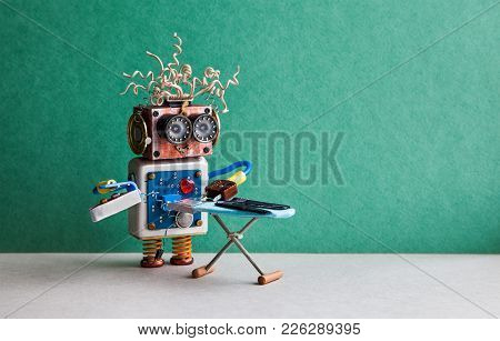 Robot helpmate ironing black pants with iron on the board. Green wall gray floor room interior. Creative design toys housework concept Copy space. stock photo