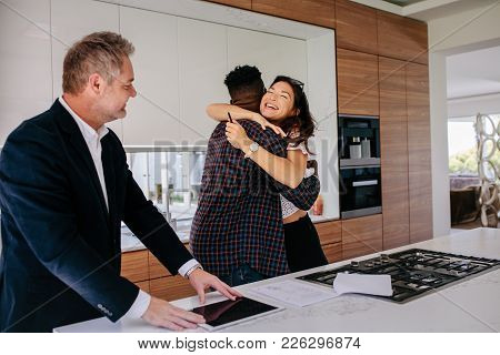 Excited couple hugging with real estate agent in kitchen of new home. Happy new property owners with realtor. stock photo