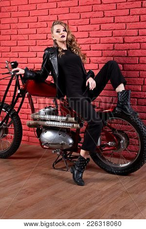 Coveted woman or girl in a leather jacket and tight pants, boots sits on a motorcycle, with an unusual hairdo and make-up on a brick red wall stock photo