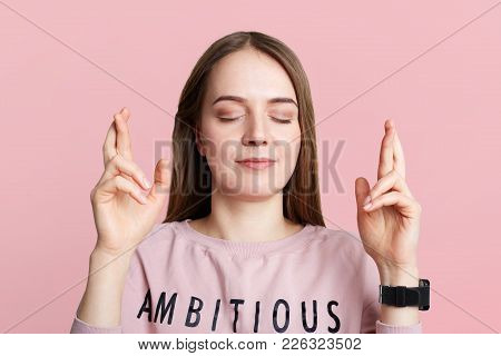 Calm restful brunette young female with make up closes eyes and crosses fingers, has great wish to pass successfuly exams, isolated over pink background. People, wish, desire and hope concept stock photo