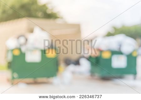 Blurred overfilled and on ground full of household waste, plastic bag, mattress, boxes after holidays. Overflowing dumpster at apartment building yard in America. Urban garbage management. stock photo