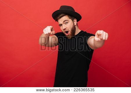 Photo of handsome fancy man wearing black t-shirt and hat having fun and pointing fingers on camera meaning hey you isolated over red background stock photo