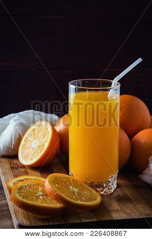A glass of orange juice, cut into pieces Orange, Oranges on a wooden board, white cloth, dark background. Beautiful Game of Light and Shadows. stock photo