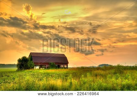 American Midwest Barn Landscape. Sunset Over A Farm Field With A Traditional Red Barn At The Horizon