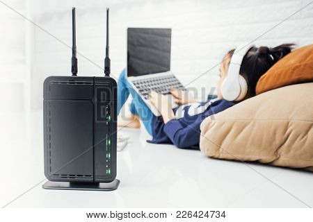 Wireless router and kids using a laptop in home. router wireless broadband home laptop computer phone wifi concept stock photo