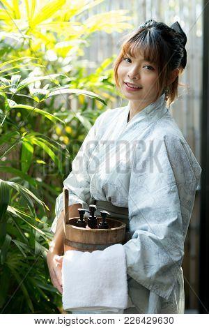 Onsen series: Asian woman holding wooden bucket in onsen stock photo