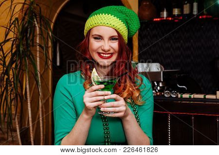 Young girl celebrate St. Patrick's Day. Woman have fun at the bar. A beautiful girl in a green hat and dress drinks a green cocktail. stock photo