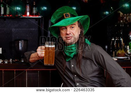 The One man celebrate St. Patrick's Day. He has fun at the bar with beer in his hand. He is dressed in carnival headgear. stock photo