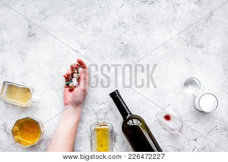 Hungover syndrome. Alcoholism. Glass, bottle and pills on grey background top view. stock photo