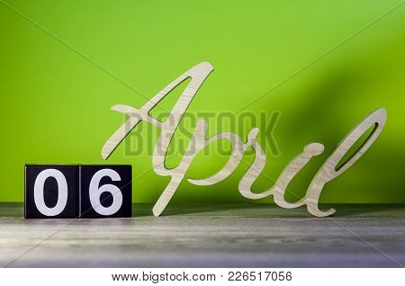 April 6th. Day 6 of month, calendar on wooden table and green background. Spring time, empty space for text. stock photo