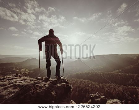 Disabled man with forearm crutches on the edge. View over the hilly ladscape in summer evening. Hurt leg on bandage with crutches stock photo