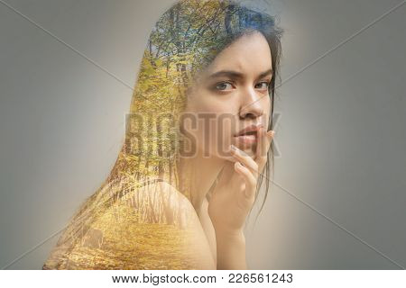 Sensible glance. Young calm beautiful woman sitting alone with her fingers touching the lips and looking into the distance stock photo