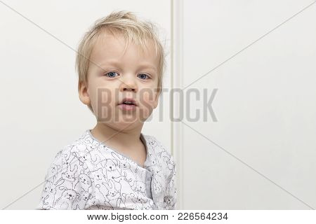 Playful disheveled cute baby looking at camera against white background. Copy space. stock photo