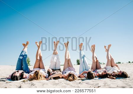 Beautiful happy slim stylish sexy young girls lying down on the sand beach and putting their feet up. legs. Party in Style boho. Maiden evening Hen-parties. Bachelorette. Close up. Portrait stock photo