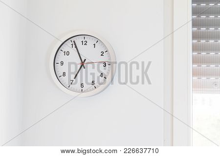 it's seven o'clock already, time to wake up for breakfast, modern white metallic alarm clock on modern white wall background stock photo
