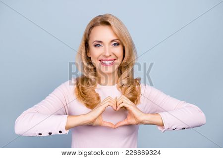 Portrait of pretty, charming, nice, attractive woman with beaming smile with curly hair showing heart figure, love symbol with fingers, isolated on grey background stock photo