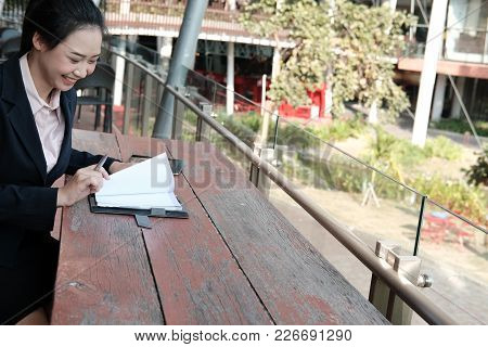 asian businesswoman reading note ourdoors. young female entrepreneur sitting on balcony. freelance woman working on terrace. people lifestyle concept stock photo