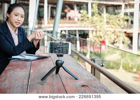 asian businesswoman use smartphone for online live streaming. woman recording video blog. vlogger presenting business vlog. stock photo