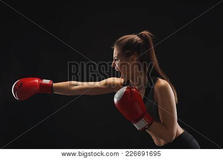 Side view of emotional young woman with boxing gloves and standing in position, ready to fight, copy space. Studio shot on black background, low key. Kickboxing and fight sport concept stock photo