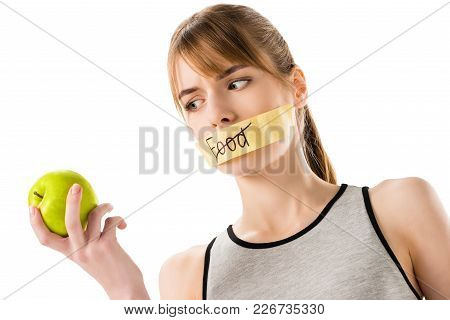 young woman with stick tape with striked through word food covering mouth looking at apple in hand isolated on white stock photo