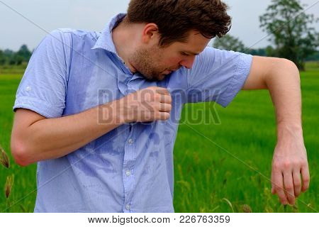 Man with hyperhidrosis sweating very badly under armpit in blue shirt because of hot weather. Travelling in asia thailand with backpacker stock photo