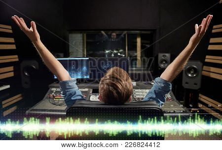 music, technology, people and equipment concept - happy man at mixing console in sound recording studio stock photo