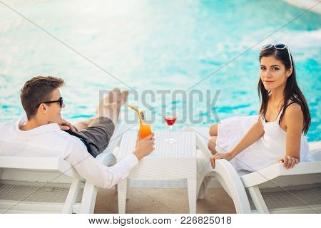 Positive happy couple relaxing by the pool in luxury summer vacation resort.Drinking cocktails.Enjoying time together in spa wellness center.Summertime relaxation.Travel, honeymoon,pampering concept stock photo