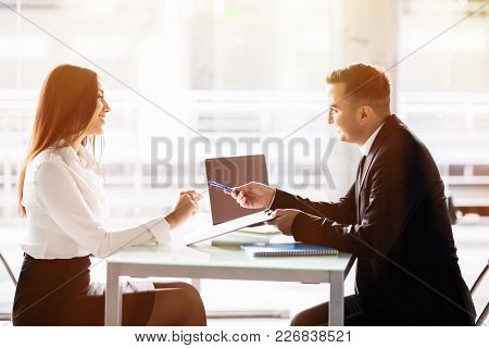 Business man and business woman sign a contract. Satisfied with loan terms woman singing contract when sitting at desk in front of male bank employee at office. stock photo