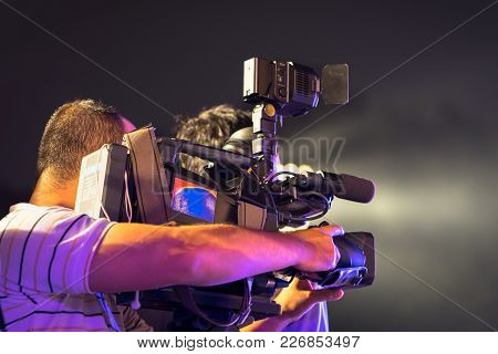 Back view of professional television camera in event at night. stock photo