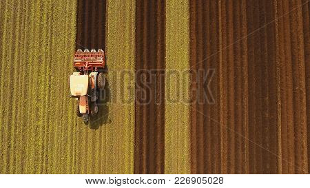 Farmer In Tractor Preparing Land With Seedbed Cultivator In Farmlands. Tractor Plows A Field. Agricu