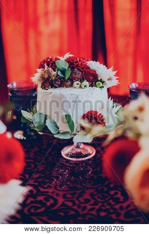 Wedding cake on the background of decor in a burgundy color in the restaurant with flowers stock photo
