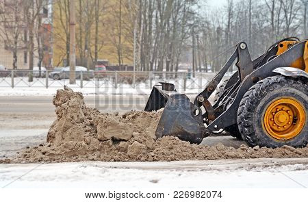 Part of a wheel and ladle of the tractor which removes a big heap of snow with sand and reagents from the carriageway on stock photo