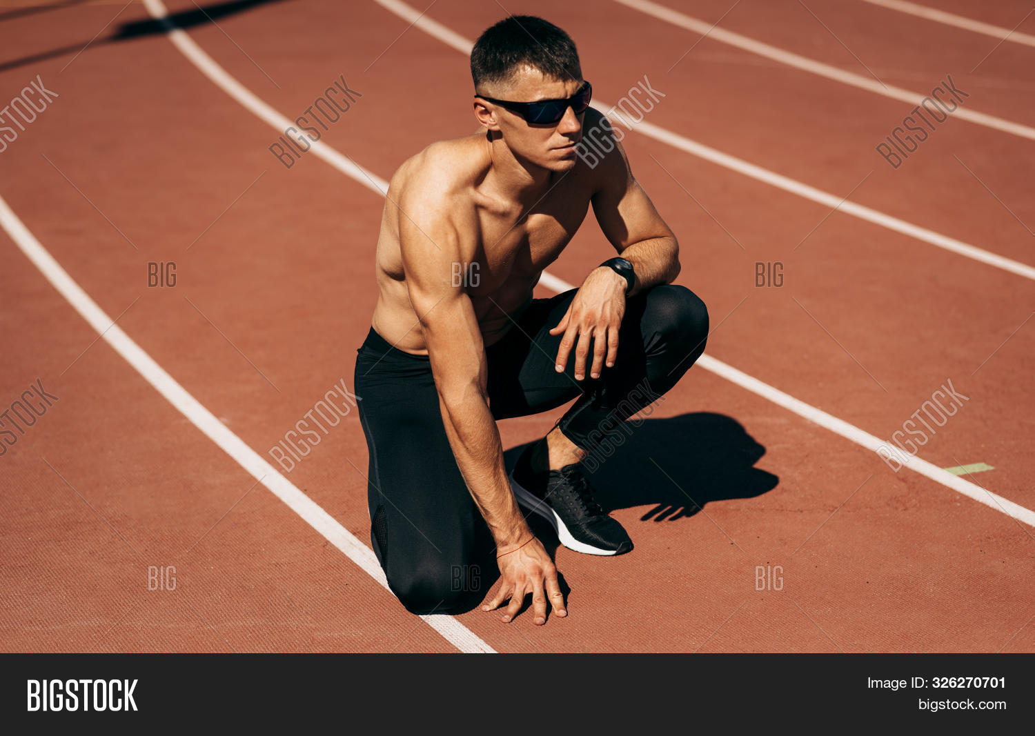 Shirtless Fit Man Preparing For Running On Racetrack At Stadium. Male Runner Sprinting During Traini
