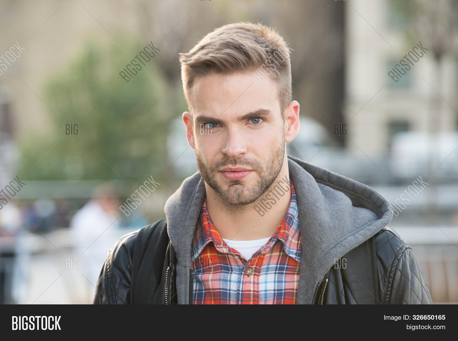 Handsome guy portrait. Facial hair and skin care concept. Handsome face. Masculine appearance. Handsome man unshaven face and stylish hair. Caucasian man urban background. Bearded man in casual style.