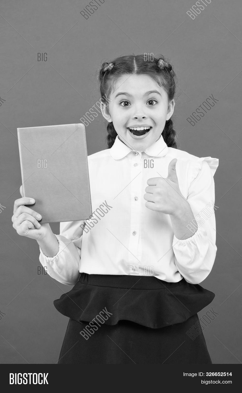 Liking Her Idea. Happy Schoolgirl Got Main Idea Of Book. Adorable Little Girl With Book Showing Ok S