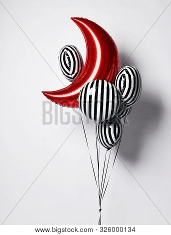 Bunch of big black and white stripes balloons  and red moon metallic balloon object for birthday party on a white background stock photo