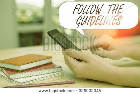 Conceptual hand writing showing Follow The Guidelines. Business photo text Manual of Style Follow a Specified Rule Accordingly woman using smartphone and technological devices inside the home. stock photo