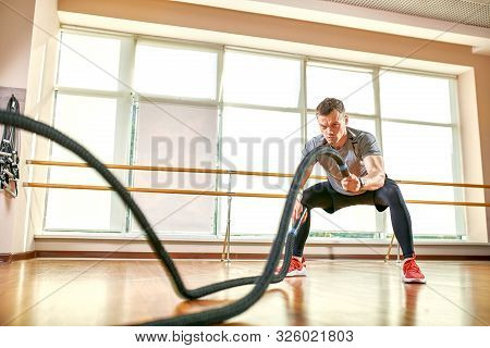 Young man working out with battle ropes at a gym stock photo
