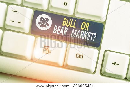 Handwriting text writing Bull Or Bear Market Question. Concept meaning asking someone about his marketing method White pc keyboard with empty note paper above white background key copy space. stock photo