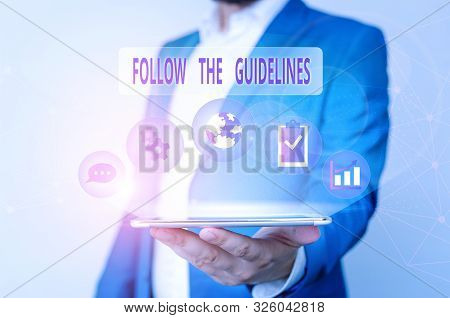 Conceptual hand writing showing Follow The Guidelines. Business photo text Manual of Style Follow a Specified Rule Accordingly Male human wear formal suit presenting using smart device. stock photo
