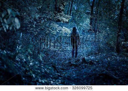 Woman walking alone on path in mystic dark forest. Lonely adult girl in strange creepy park at night in autumn. Young woman in fantasy spooky woods in twilight. Fear in scary mystery forest. stock photo