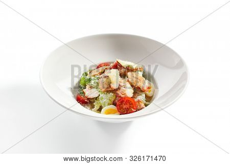 Delicious caesar with chicken fillet closeup. North american cuisine restaurant dish. Healthy food, tasty appetizer isolated on white background. Traditional salad with bird meat, tomatoes and eggs stock photo