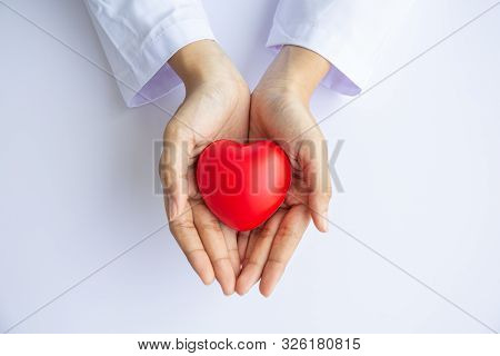 Woman doctor hands holding red heart on white background donate for hospital care concept. world heart day and world health day, CSR community, foster support patient. stock photo