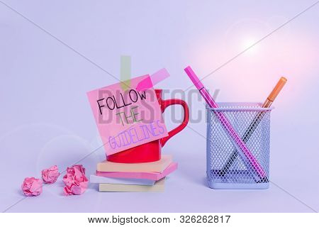 Word writing text Follow The Guidelines. Business concept for Manual of Style Follow a Specified Rule Accordingly Cup pens holder note banners stacked pads paper balls pastel background. stock photo