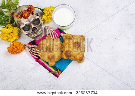 Mexican dia de los muertos Day of the Dead background. Skull, yellow and orange cempasuchil flowers or marygold and pan de muertos. Traditional festive altar offering. stock photo