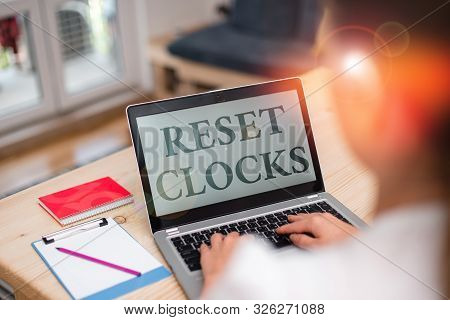 Handwriting text Reset Clocks. Concept meaning To revisit return to or recreate a time or era from the past woman laptop computer office supplies technological devices inside home. stock photo