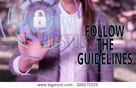 Handwriting text Follow The Guidelines. Concept meaning Manual of Style Follow a Specified Rule Accordingly Female human wear formal work suit presenting presentation use smart device. stock photo