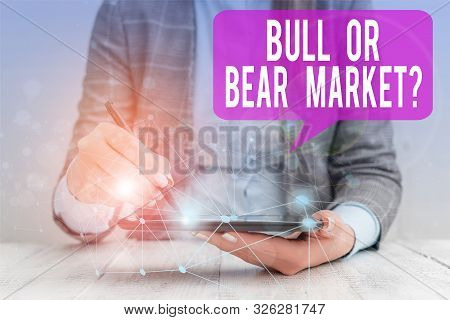 Word writing text Bull Or Bear Market Question. Business concept for asking someone about his marketing method Female human wear formal work suit presenting presentation use smart device. stock photo